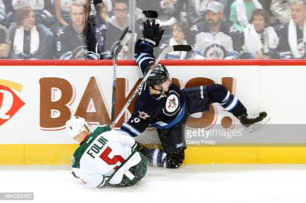 Christian Folin of the Minnesota Wild and Andrew Copp of the Winnipeg Jets fall to the ice after colliding along the boards during first period...
