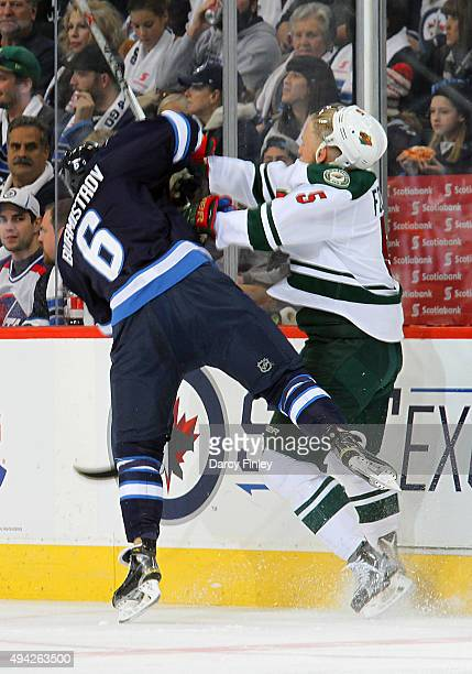 Christian Folin of the Minnesota Wild sends Alexander Burmistrov of the Winnipeg Jets flying after a first period check along the boards at the MTS...