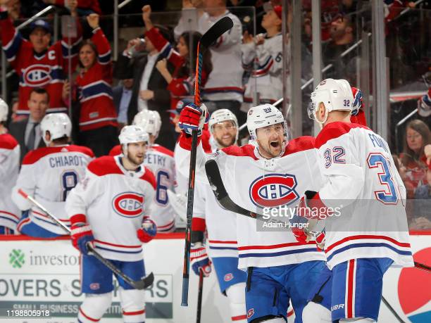 Christian Folin of the Montreal Canadiens is congratulated by teammate Tomas Tatar after scoring a third period goal against the New Jersey Devils on...