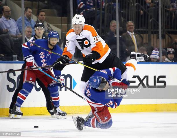 Christian Folin of the Philadelphia Flyers hits Brady Skjei of the New York Rangers during the third period at Madison Square Garden on January 29...