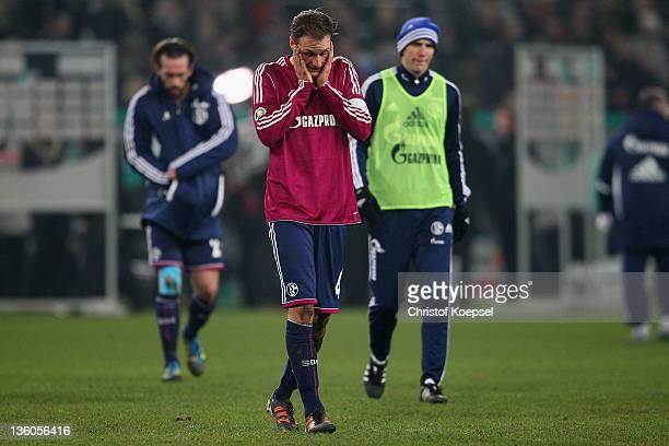 Christian Fuchs, Benedikt Hoewedes and Christoph Moritz of Schalke look dejected after the DFB Cup round of sixteen match between Borussia...