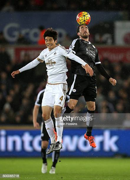 Christian Fuchs of Leicester City and Ki SungYeung of Swansea City compete for the ball during the Barclays Premier League match between Swansea City...
