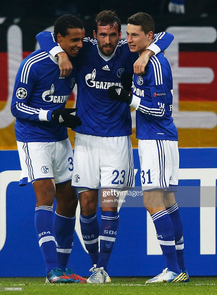 Christian Fuchs (C) of Schalke celebrates with his team mates Joel Matip (L) and Julian Draxler after scoring his team's first goal during the UEFA Champions League group B match between FC Schalke 04 and Olympiacos FC at Veltins-Arena on November 21, 2012 in Gelsenkirchen, Germany.