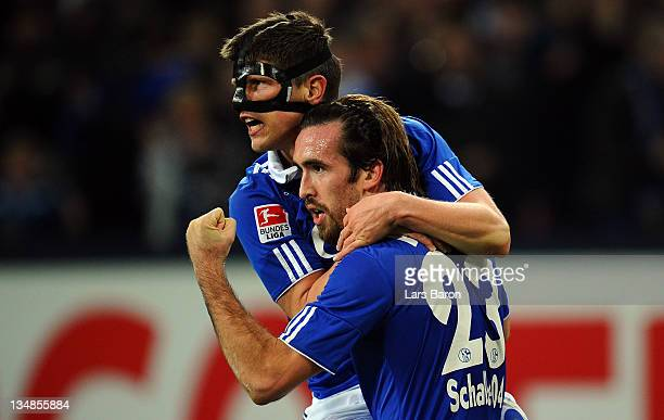 Christian Fuchs of Schalke celebrates with team mate Klaas Jan Huntelaar after scoring his teams second goal during the Bundesliga match between FC...
