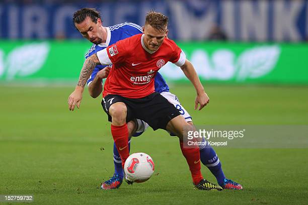Christian Fuchs of Schalke challenges Eugen Polanski of Mainz during the Bundesliga match between FC Schalke 04 and FSV Mainz at VeltinsArena on...