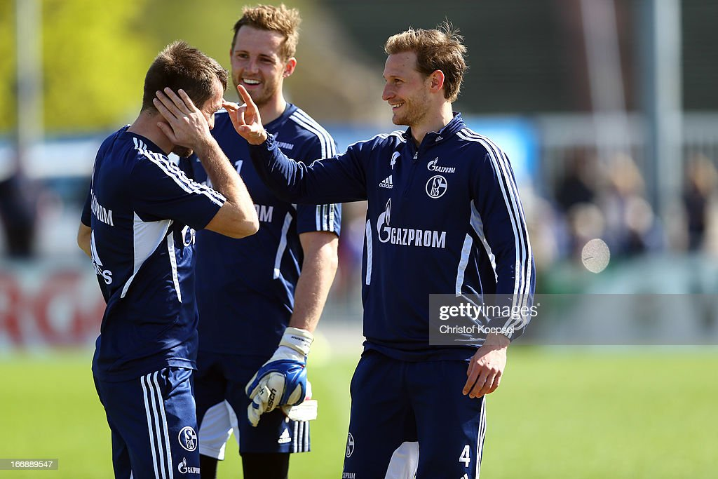 Christian Fuchs, Ralf Faehrmann and Benedikt Hoewedes make nonsense during the FC Schalke 04 training session at their training ground on April 18, 2013 in Gelsenkirchen, Germany.