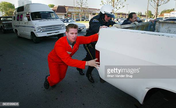 Christian Galloway 28 of Woodland Hills left helps two Burbank police motorcycle officers push a truck belonging to John Mallon of Sherman Oaks down...