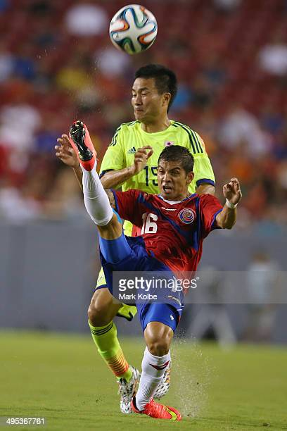 Christian Gambo of Costa Rica clears the ball under pressure from Yasuyuki Konno of Japan during the International Friendly Match between Japan and...