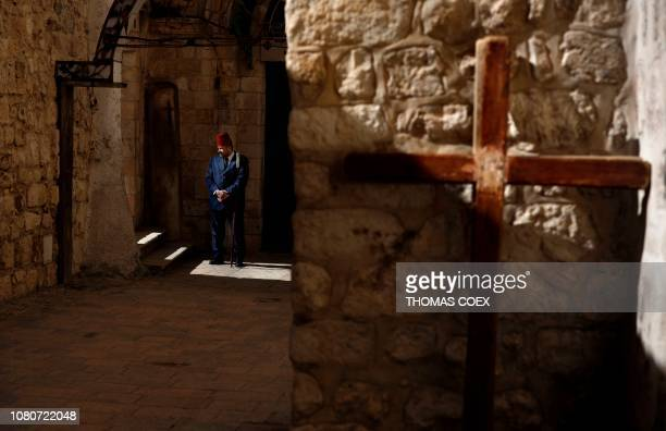 Christian gatekeeper stands near the IX station of the Via Dolorosa outside the Church of the Holy Sepulchre which tradition believes to be the spot...