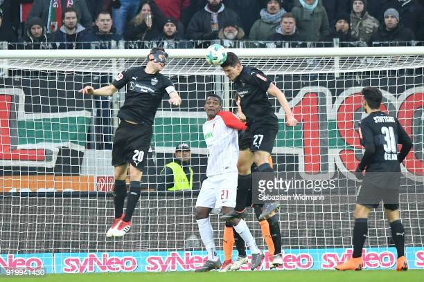 Christian Gentner and Mario Gomez of Stuttgart jump for a header as Sergio Cordova of Augsburg watches during the Bundesliga match between FC...