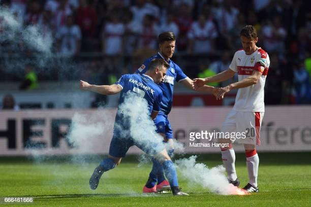 Christian Gentner of Stuttgart Benedikt Gimber and Dennis Kempe of Karlsruhe evade a signal rocket after the Second Bundesliga match between VfB...