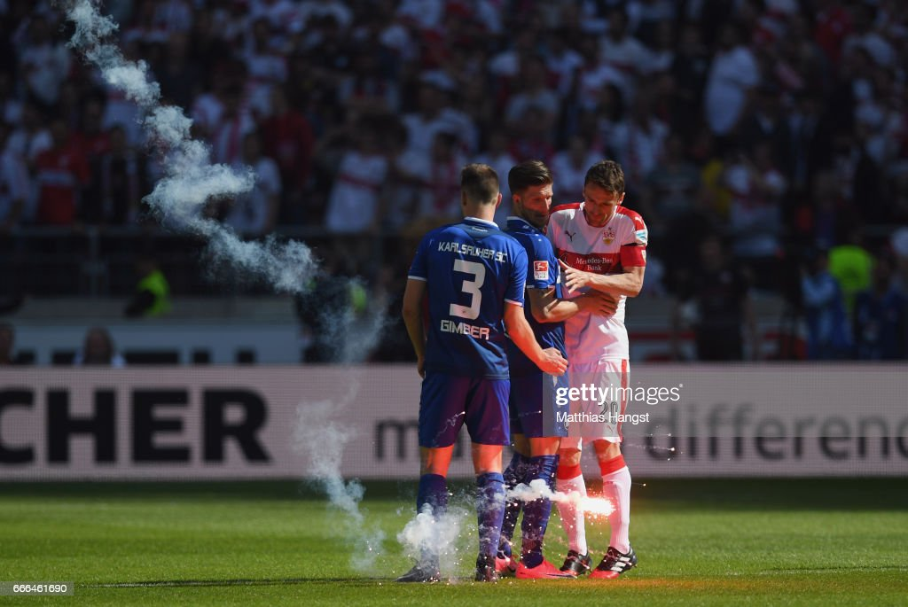 Christian Gentner of Stuttgart, Benedikt Gimber #3 and Dennis Kempe of Karlsruhe evade a signal rocket after the Second Bundesliga match between VfB Stuttgart and Karlsruher SC at Mercedes-Benz Arena on April 9, 2017 in Stuttgart, Germany.