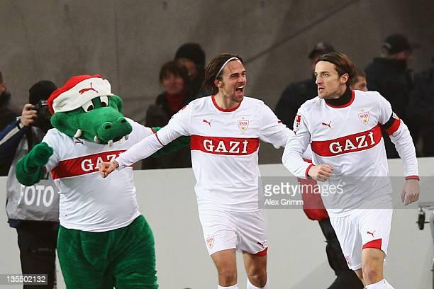 Christian Gentner of Stuttgart celebrates his team's first goal with team mate Martin Harnik and mascot 'Fritzle' during the Bundesliga match between...