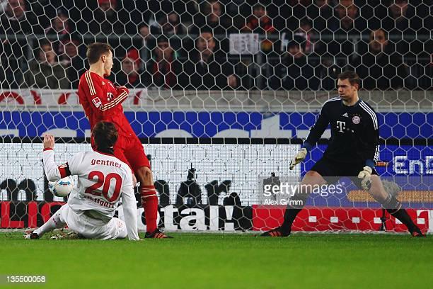 Christian Gentner of Stuttgart scores his team's first goal against Holger Badstuber and goalkeeper Manuel Neuer of Muenchen during the Bundesliga...