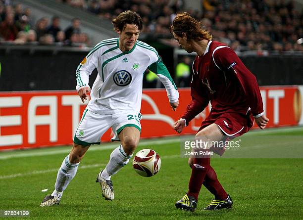 Christian Gentner of Wolfsburg and Cristian Ansaldi of Kazan compete for the ball during the UEFA Europa League round of 16 second leg match between...