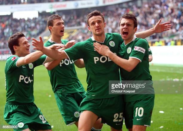 Christian Gentner of Wolfsburg celebrates his first goal with team mates Sascha Riether Edin Dzeko and Zvjezdan Misimovic during the Bundesliga match...