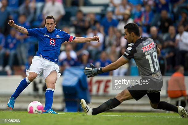 Christian Gimenez of Cruz Azul vies for the ball with Sergio Garcia goalkeeper of Gallos Blancos during their Mexican Apertura 2012 tournament...