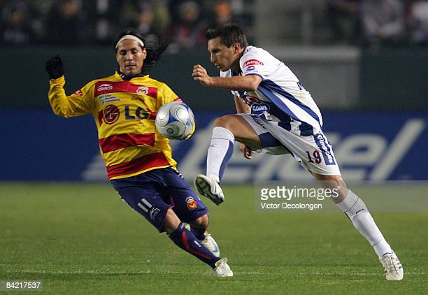 Christian Gimenez of Pachuca FC plays the ball as Hugo Droguett of Morelia defends in the second half during their InterLiga match at The Home Depot...
