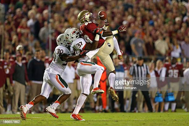 Christian Green of the Florida State Seminoles misses a catch defended by Ladarius Gunter and AJ Highsmith of the Miami Hurricanes during a game at...