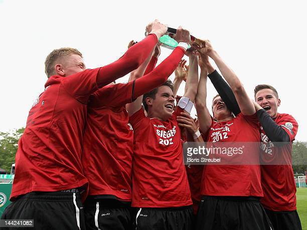 Christian Guenter of Freiburg and his team mates celebrate with the trophy after winning the DFB Juniors Cup final between Hertha BSC Berlin and SC...