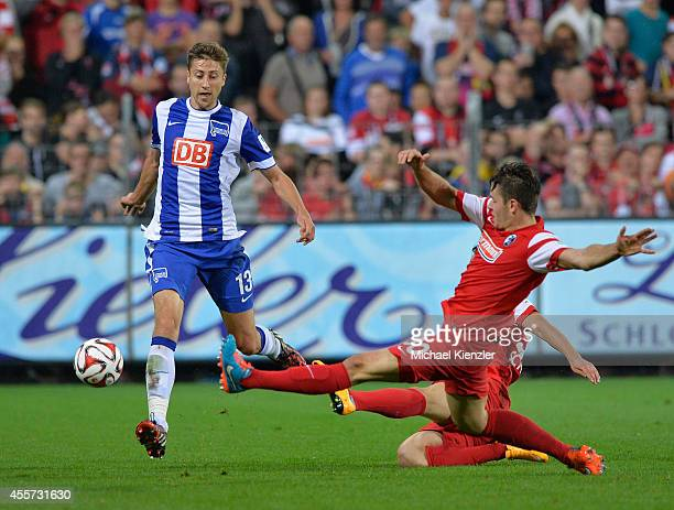 Christian Guenter of Freiburg challenges Jens Hegeler of Hertha BSC during the Bundesliga match between SC Freiburg and Hertha BSC at Mage Solar...