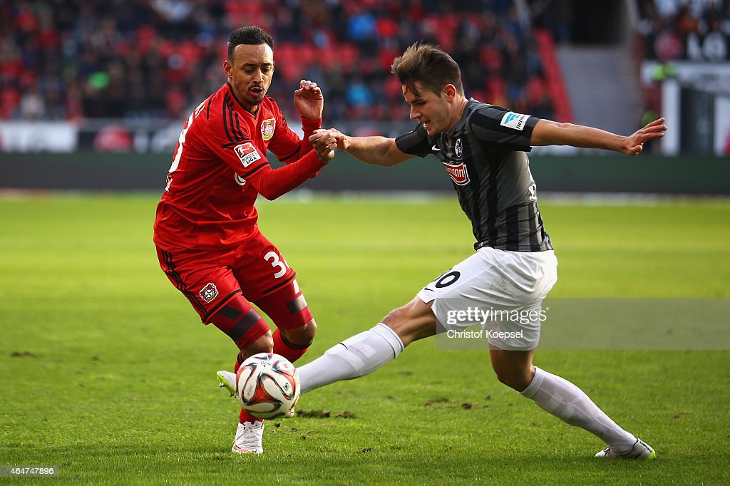 Christian Guenter of Freiburg (R) challenges Karim Bellarabi of Leverkusen (L) during the Bundesliga match between Bayer 04 Leverkusen and SC Freiburg at BayArena on February 28, 2015 in Leverkusen, Germany.