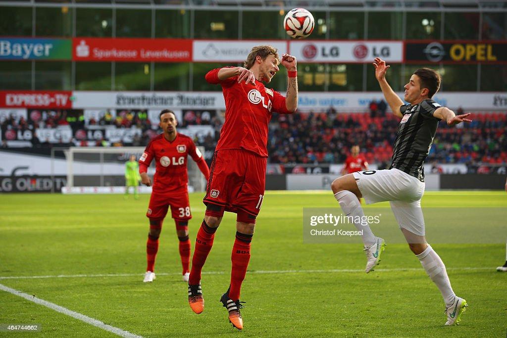 Christian Guenter of Freiburg (R) challenges Stefan Kiessling of Leverkusen (L) during the Bundesliga match between Bayer 04 Leverkusen and SC Freiburg at BayArena on February 28, 2015 in Leverkusen, Germany.