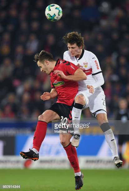 Christian Guenter of Freiburg jumps for a header with Benjamin Pavard of Stuttgart during the Bundesliga match between SportClub Freiburg and VfB...