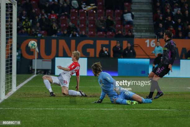 Christian Guenter of Freiburg scores the team`s first goal and Martin Hinteregger of Augsburg and Goalkeeper Marvin Hitz of Augsburg look on during...