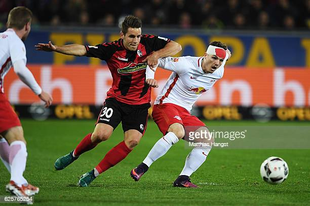 Christian Guenter of SC Freiburg challenges Marcel Sabitzer of RB Leipzig during the Bundesliga match between SC Freiburg and RB Leipzig at...
