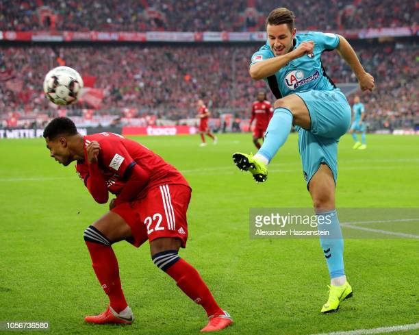 Christian Gunter of Freiburg clears the ball while under pressure from Serge Gnabry of Bayern Munich during the Bundesliga match between FC Bayern...