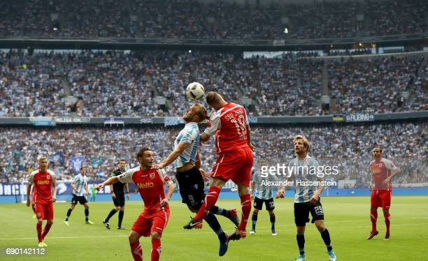 Christian Gytkjaer of 1860 Muenchen and Marvin Knoll of Jahn Regensburg jump to head for the ball during the Second Bundesliga Playoff second leg...