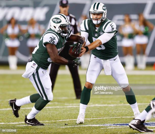 Christian Hackenberg hands off to Elijah McGuire of the New York Jets against the Philadelphia Eagles during their preseason game at MetLife Stadium...