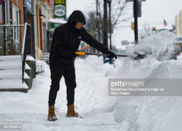 Christian Haney shovels snow from the sidewalk in front of Regina's Salon, his mothers business on Penn Ave in West Reading. During a snow storm in...