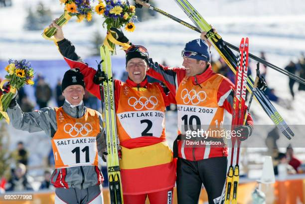 Christian Hoffmann of Austria Johann Muehlegg of Spain and Mikhail Botvinov of Austria celebrate on the award stand following the Men's 30 kilometer...