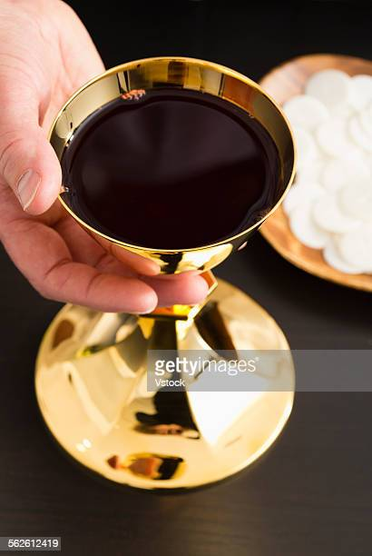 Christian holy communion, mans hand holding gold chalice with wine, communion wafer on plate
