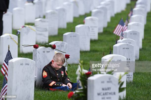 Christian Jacobs sits against the headstone of his father US Marine Corps Sgt Christopher James Jacobs as he visits in observance of Memorial Day at...