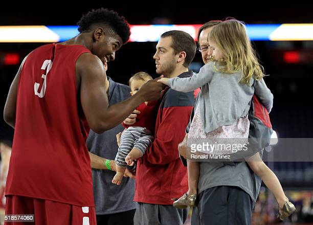 Christian James of the Oklahoma Sooners talks with Avery Ciklin as she is being held by her grandfather head coach Lon Kruger of the Sooners during a...