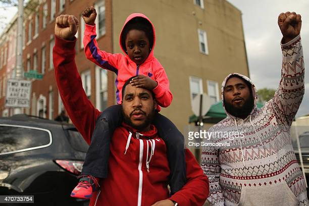 Christian Johnson Sr holds his daughter Chrisette Johnson on his shoulders and puts his fist in the air as a sign of 'black power' during a protest...