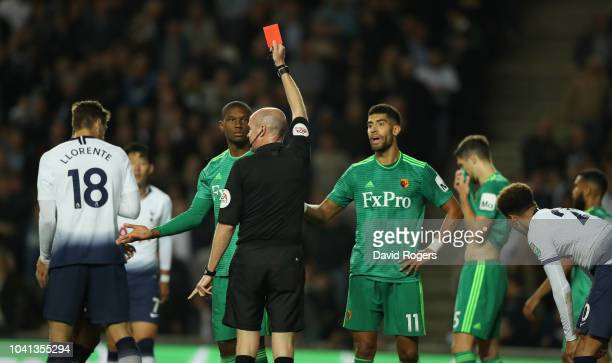 Christian Kabasele of Watford is shown the red card by referee Lee Mason after tackling Dele Alli during the Carabao Cup Third Round match between...