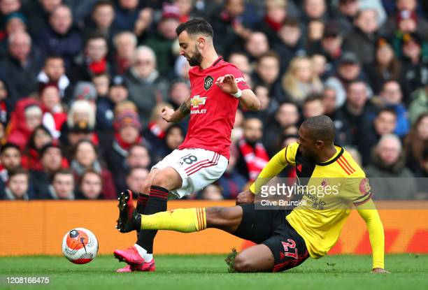 Christian Kabasele of Watford tackles Bruno Fernandes of Manchester United during the Premier League match between Manchester United and Watford FC...