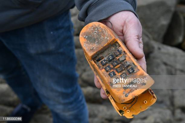 Christian KervelleLety a voluntary of the French association Ar Viltansou shows a Garfield phone near the entry of a partially submerged cave only...