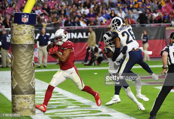 Christian Kirk of the Arizona Cardinals runs into the goal post while attempting to make a catch as Marqui Christian and Nickell Robey-Coleman of the...