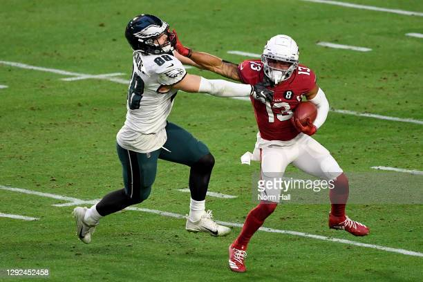 Christian Kirk of the Arizona Cardinals straight arms Dallas Goedert of the Philadelphia Eagles while returning a punt during the fourth quarter at...