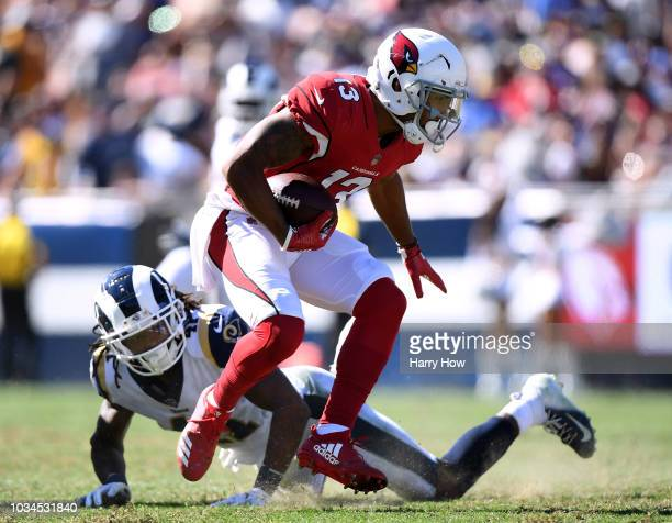 Christian Kirk of the Arizona Cardinals takes a hit from Marqui Christian of the Los Angeles Rams during the fourth quarter at Los Angeles Memorial...