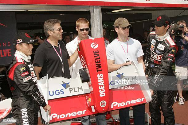 Christian Klein, George Clooney, Brad Pitt, Matt Damon and Mark Webber pose during a guided tour of the Jaguar garage as the official guests of...