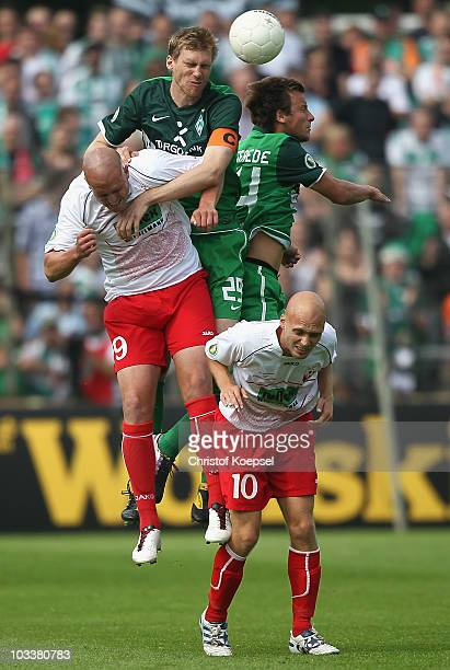 Christian Knappmann of Ahlen Per Mertesacker and Philipp Bargfrede of Bremen and Nils Ole Book of Ahlen go up for a header during the DFB Cup first...