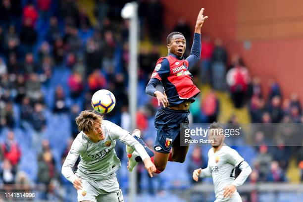 Christian Kouamé of Genoa jumps between Nicolò Zaniolo and Alessandro Florenzi of Roma during the Serie A match between Genoa CFC and AS Roma at...