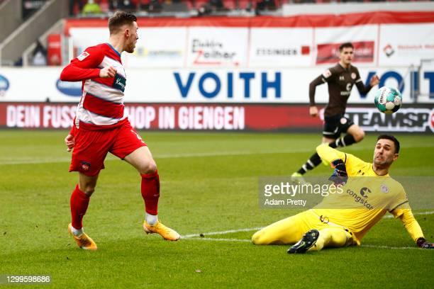 Christian Kuehlwetter of Heidenheim scores his team's second goal against goalkeeper Dejan Stokanovic of St. Pauli during the Second Bundesliga match...