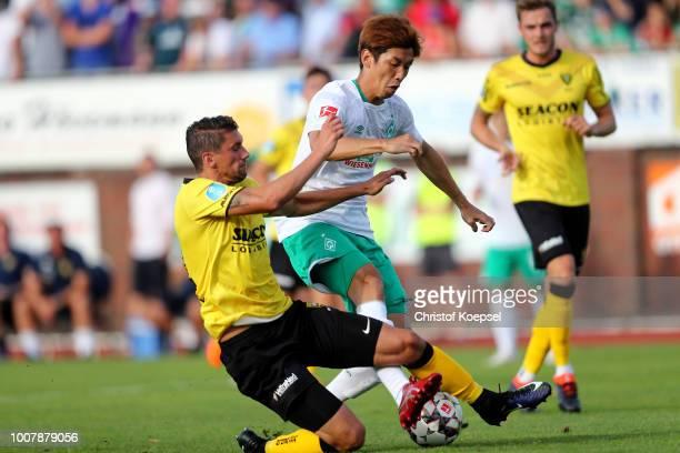 Christian Kum of Venlo challenges Yuya Osako of Bremen during the Pre Season Friendly Match between VVV Venlo and Werder Bremen at...